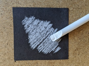 Dark paper on a writing board. There is a chalk scribble on the paper. The stick of chalk is next to the scribble.