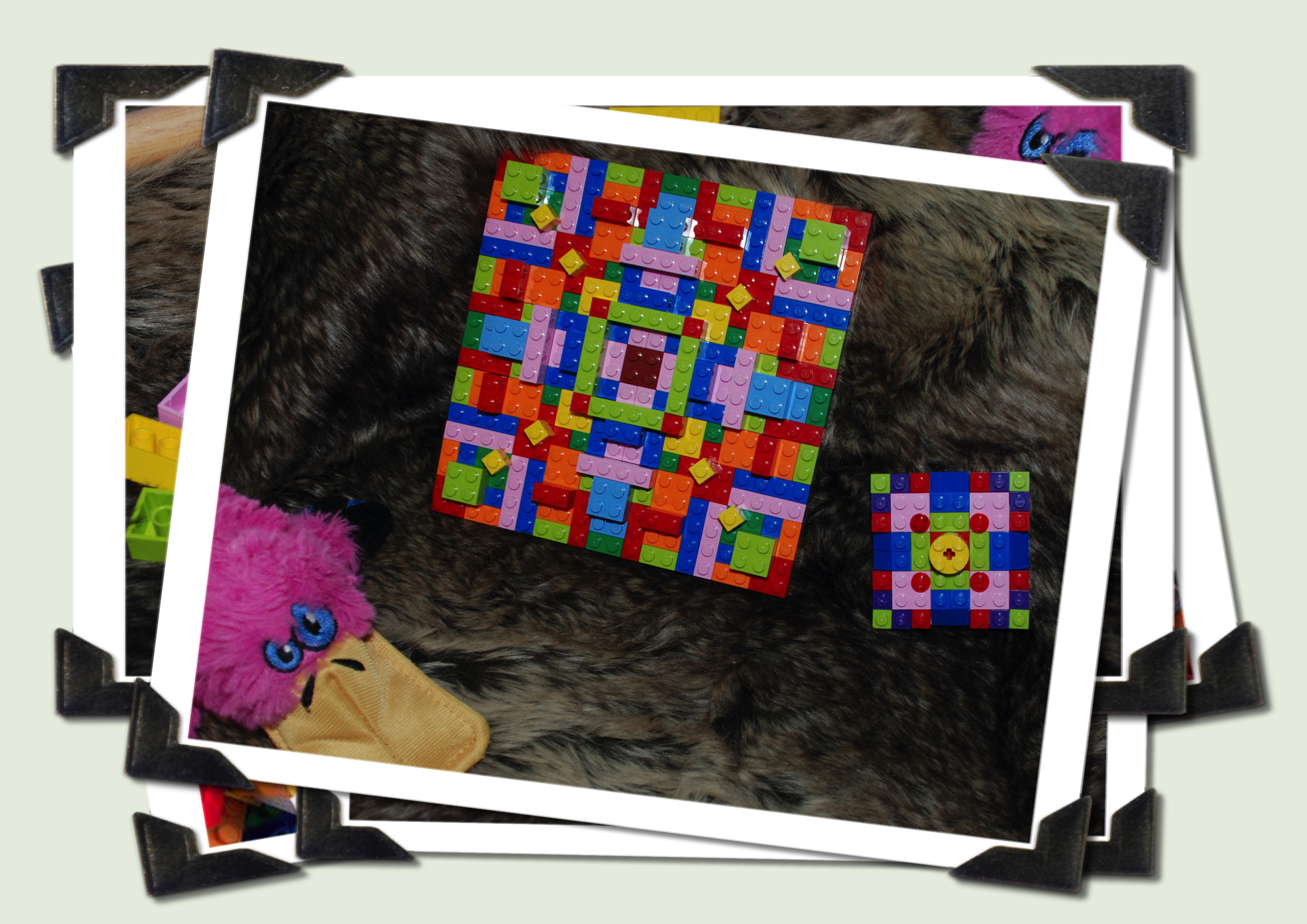 A pile of photos with only the top picture visible. The photo is Anno the pink toy platypus next to two lego mosaic patterns - one large