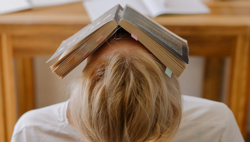 Person leaning back in their chair with their head hanging over the back. they have an open book placed on their face. it is photographed from behind the person.