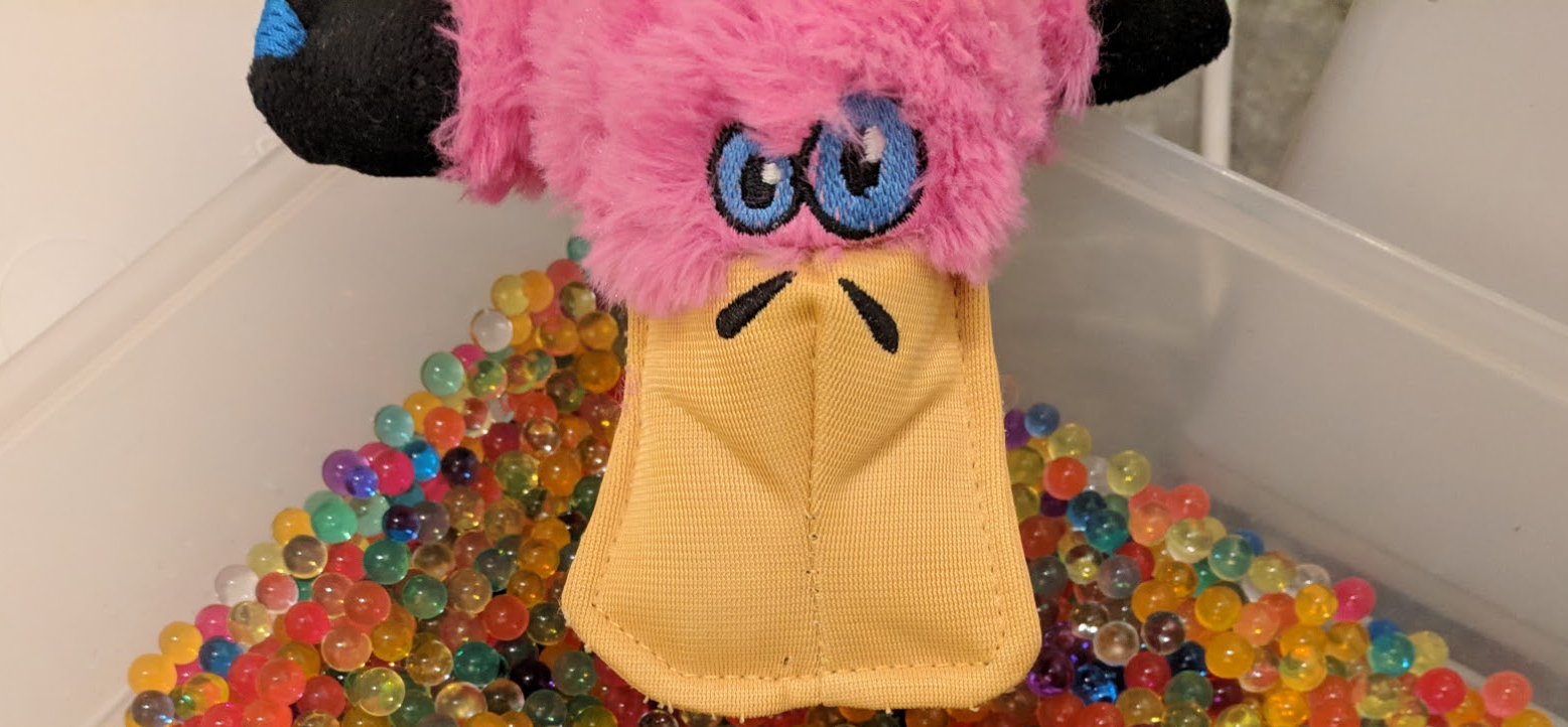 A pink and furry platypus toy, looking into a plastic box with brightly coloured water beads in it
