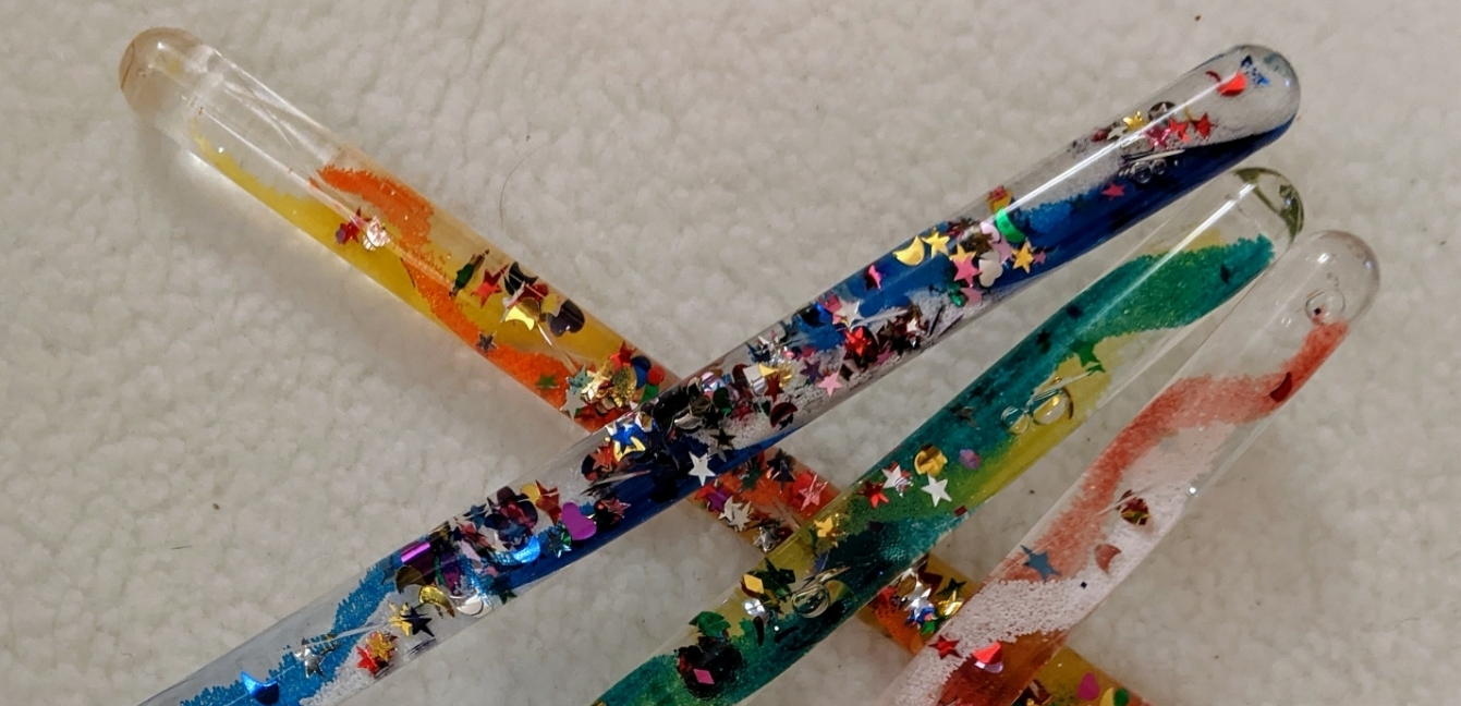 Four Glitter sticks crossed over each other. Glitter sticks are long clear plastic tubes filled with tiny colourful beads and glitter stars and shapes. they move up and down the tube as you change their position