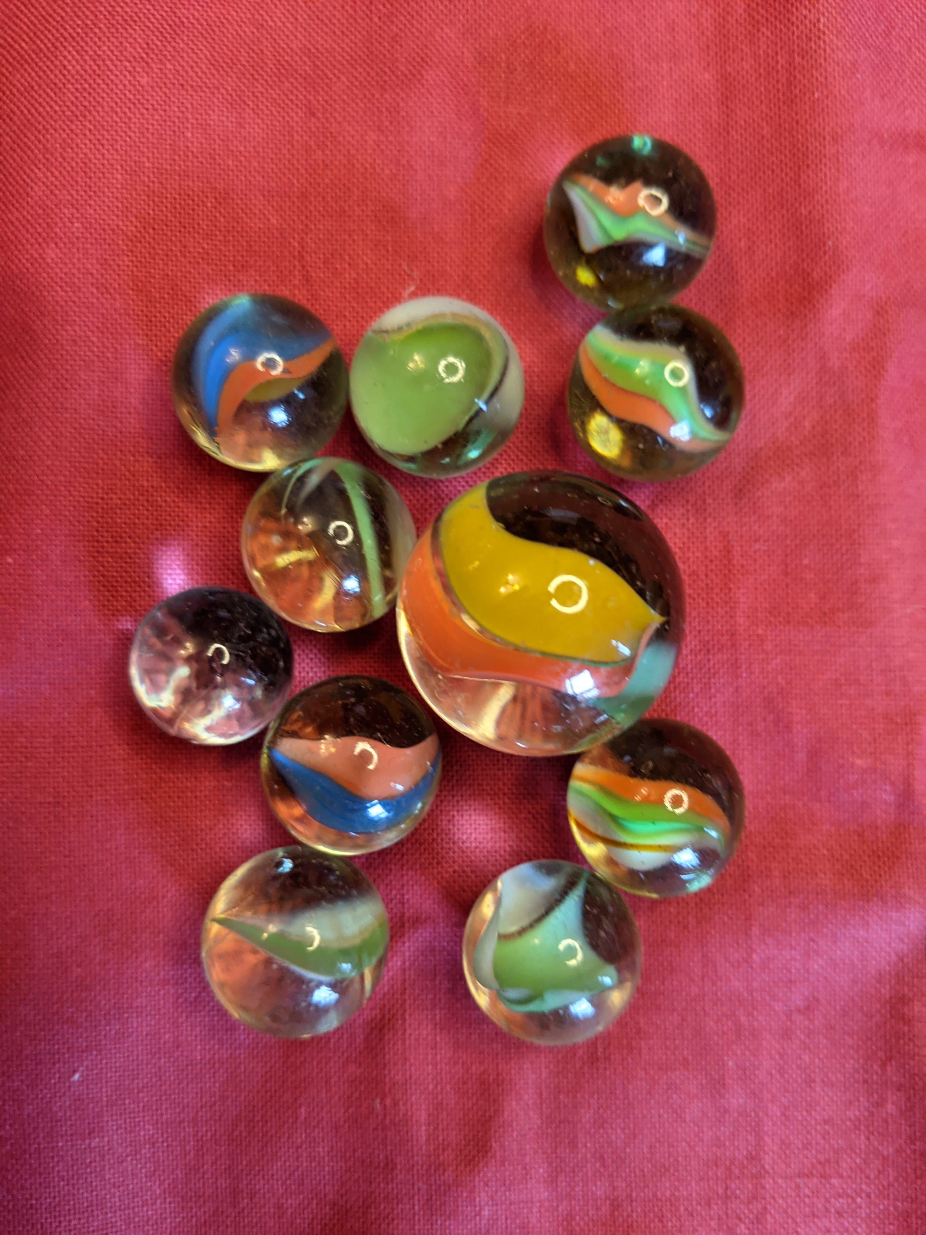 A selection of small marbles with one big marble. Each has a ribbon of colour in the middle of the glass.