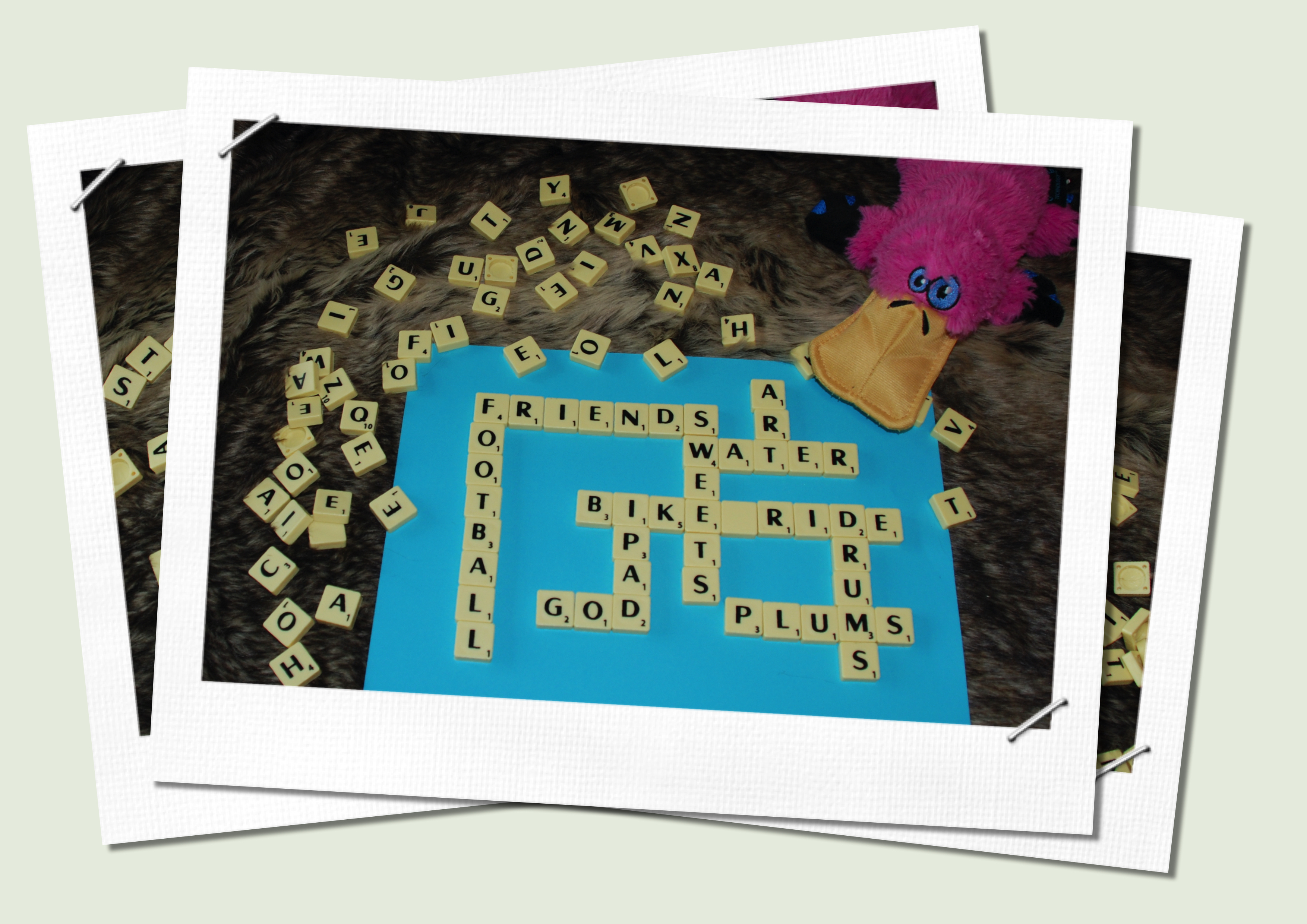 Image shows a representation of a pile of pictures. the top one shows the standard use of scrabble, with the cheat with blank tiles mentioned in the  text. Anno the pink platypus toy is also in the photo.